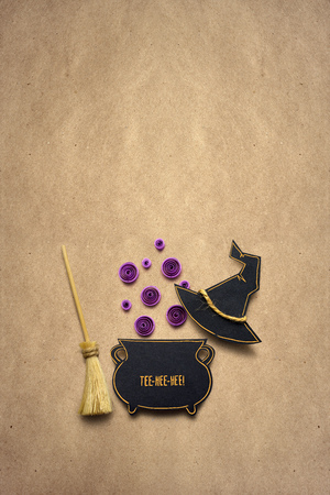 Creative halloween concept photo of witches staff and a boiler made of paper on brown background.
