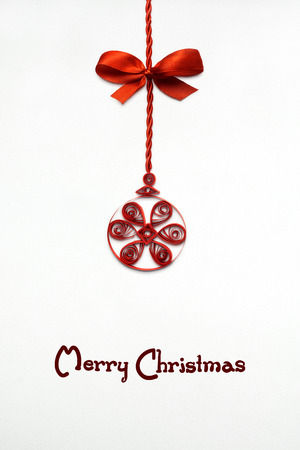 Creative concept photo of a christmas ball made of paper quilling on white background. Stock Photo