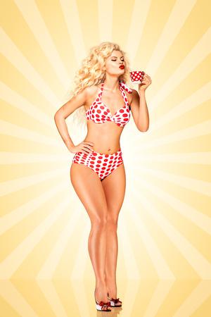 Mooi pinup bikini model, houden ta kopje koffie op kleurrijke abstracte cartoon stijl achtergrond. Stockfoto