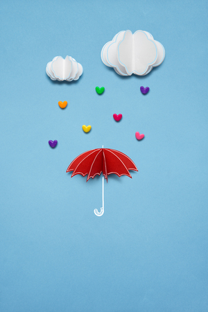 Creative valentines concept photo of umbrella with hearts raining down on white background.