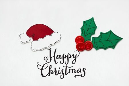 Creative photo of santas hat and holly berry made  of paper on white background.