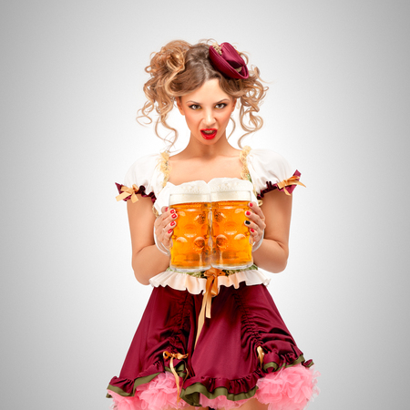 Beautiful Oktoberfest waitress wearing a traditional Bavarian dress dirndl, holding beer mugs on grey background. Stock Photo