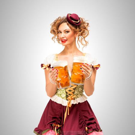 Beautiful Oktoberfest waitress wearing a traditional Bavarian dress dirndl, holding beer mugs on grey background. Stock Photo