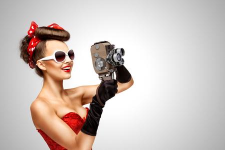 灰色の背景に古いヴィンテージの 8 mm カメラでピンナップ ガールのレトロな写真。 写真素材