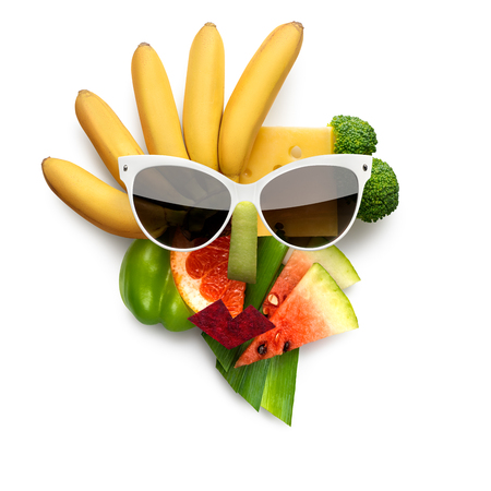 Quirky food concept of cubist style female face in sunglasses made of fruits and vegetables, on white background. Stock Photo