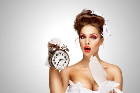 Sexy pinup bride in a vintage wedding corset holding a retro alarm clock on grey background.