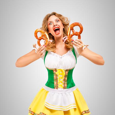 pretzel: Beautiful Oktoberfest woman wearing a traditional Bavarian dress dirndl holding pretzels, on grey background. Stock Photo