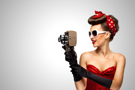 Retro photo of a pin-up girl with an old vintage 8 mm camera on grey background.