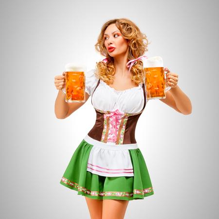 Beautiful Oktoberfest woman wearing a traditional Bavarian dress dirndl serving beer mugs on grey background. Stock Photo