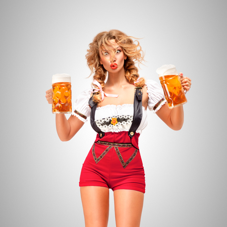 Beautiful woman wearing red jumper shorts with suspenders as traditional dirndl, serving two beer mugs on grey background. Stockfoto