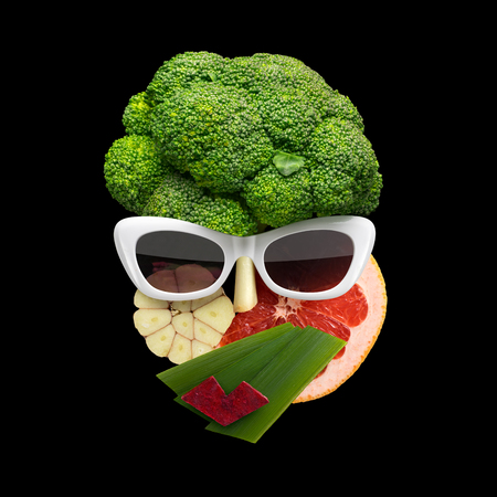 Quirky food concept of cubist style female face in sunglasses made of fruits and vegetables, on black background.