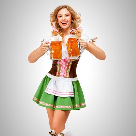 Schöne Oktoberfest Frau trägt ein traditionelles bayerisches Kleid Dirndl serviert Bier Tassen auf grauem Hintergrund. Standard-Bild - 80018030