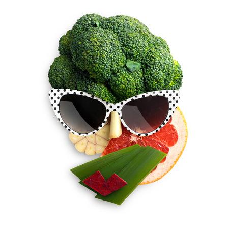 Eigenzinnig voedselconcept kubiste stijl vrouwelijk die gezicht in zonnebril van vruchten en groenten, op witte achtergrond wordt gemaakt.