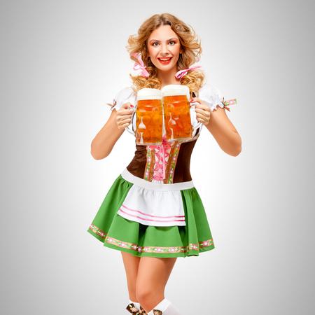 Mooie Oktoberfest vrouw draagt een traditionele Beierse jurk dirndl serveert bier mokken op grijze achtergrond.