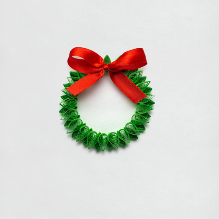 Creative concept photo of christmas wreath made of quilling paper on white background. Stock Photo
