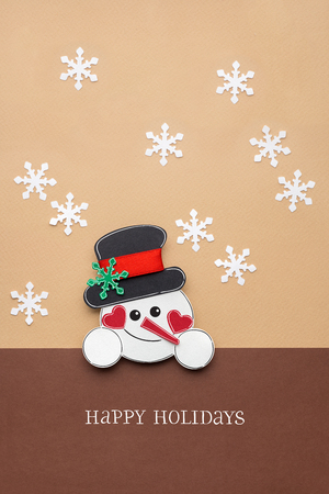 Creative photo of a snowman made of paper on brown background. Stock Photo