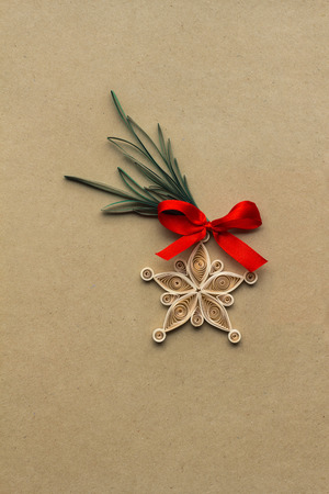 Creative christmas concept photo of a snowflake made of qulling paper on brown background.