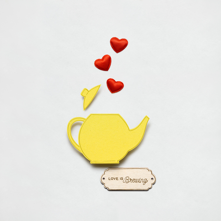 Creative valentines concept photo of a teapot made of paper on white background.