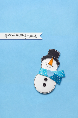 Creative photo of a snowman made of paper on blue background.