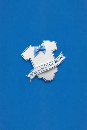 Creative concept photo of a childs jumpers made of paper on blue background. Фото со стока