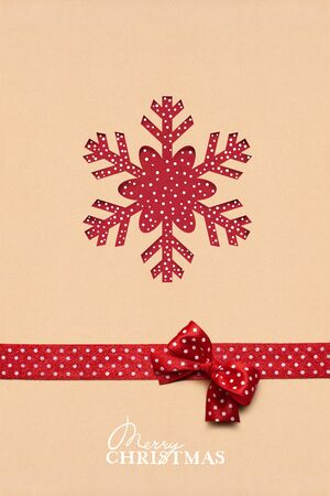 christmas decor: Creative christmas concept photo of a snowflake made of paper on brown background.