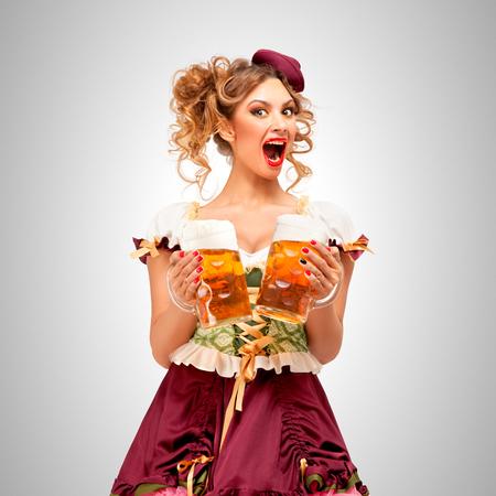 Schöne Oktoberfest Kellnerin trägt ein traditionelles bayerisches Kleid Dirndl, hält Bierkrüge auf grauem Hintergrund. Standard-Bild - 82397697