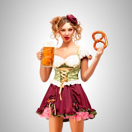 Schöne Oktoberfest Kellnerin trägt ein traditionelles bayerisches Kleid Dirndl mit einem Brezel und Bierkrug, auf grauem Hintergrund. Standard-Bild - 82417915