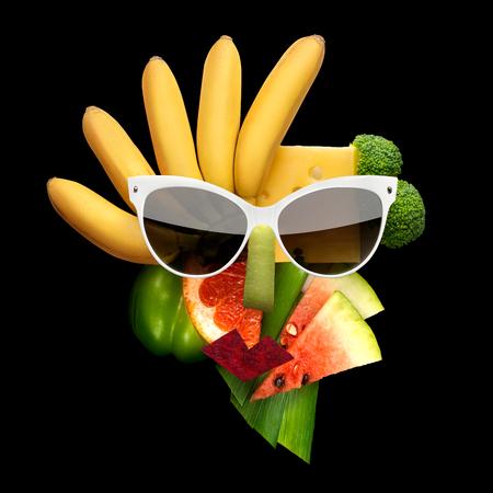 果物や野菜、黒の背景には、サングラスにキュビズム スタイル女性の顔の風変わりな食品のコンセプト。