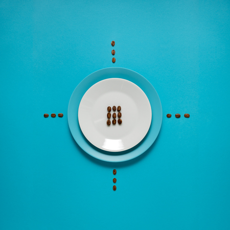 Creative concept photo of kitchenware, painted plate with food on it on blue background. Stock Photo