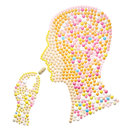 Creative medicine and healthcare concept made of pills in the shape of a human head taking a pill on white background.