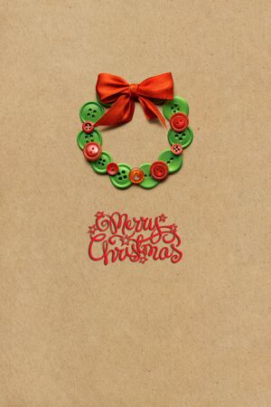 Creative concept photo of christmas wreath made of buttons on brown background.
