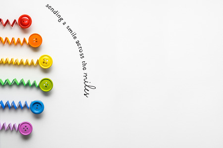 Creative concept photo of a rainbow  made of paper and buttons on grey background.