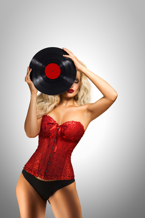 Beautiful pinup model holding retro vinyl on grey  background.