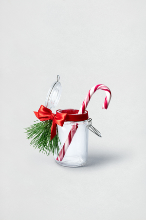 Creative concept photo of christmas candy in the bottle on white background. Stock Photo
