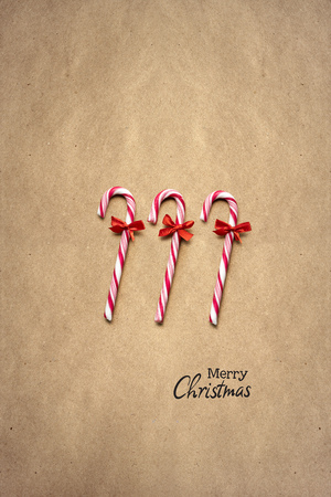 Creative concept photo of christmas lollypop candies on brown background.