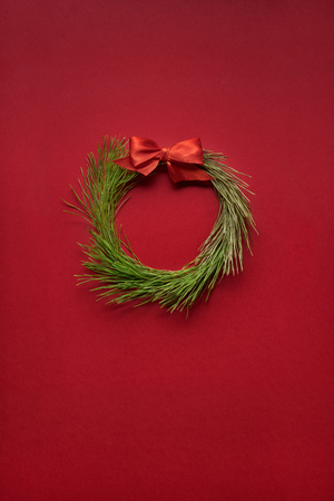 Creative concept of christmas wreath made of tree on red background.