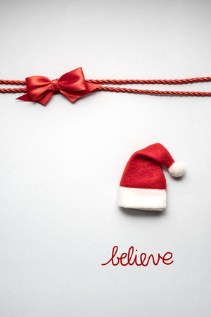 Creative concept photo of santas hat and sign grey background. Stock Photo