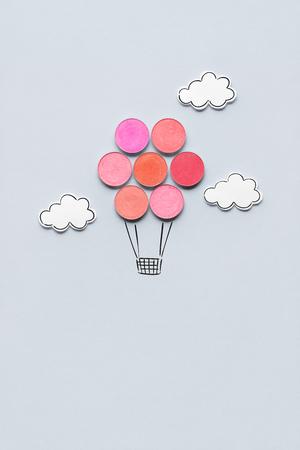 Creative concept photo of aerostat made of cosmetics on grey background.