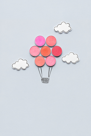 Creative concept photo of aerostat made of cosmetics on grey background.