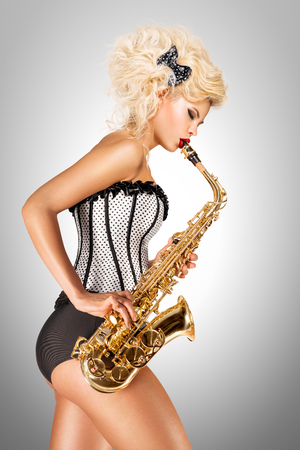 Beautiful pinup model playing saxophone on grey background.