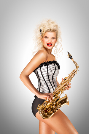 Beautiful pinup model playing saxophone on grey background.