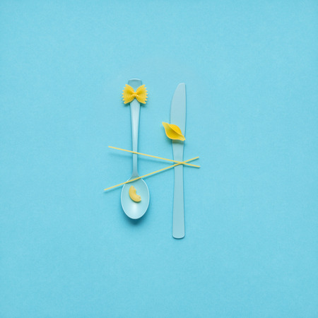 Creative still life photo of fork and spoon with raw pasta on blue background.