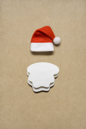 Creative concept photo of santas hat and beard on brown background.