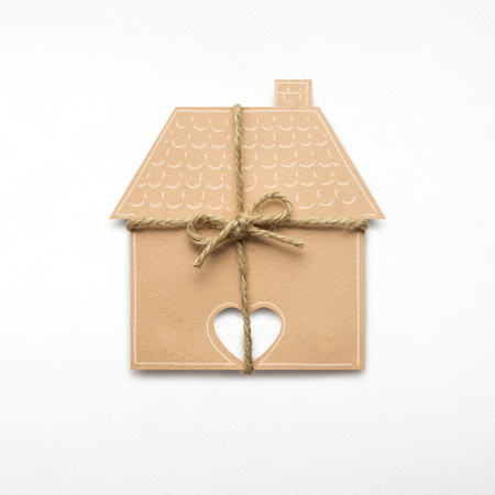Creative concept photo of a house with a bow made of paper on white background. Reklamní fotografie