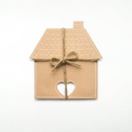 Foto criativa do conceito de uma casa com um arco feito de papel no fundo branco. Foto de archivo - 93810010
