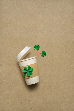 Creative St. Patricks Day concept photo of take away coffee cup with shamrocks made of paper on brown background. Stock Photo