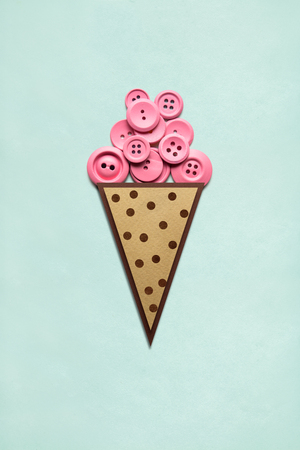 Creative concept photo of ice cream with buttons made of paper on mint background.