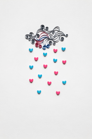 Creative valentines concept photo of cloud with hearts raining down on white background.