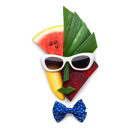 Creative concept of cubist style female face in sunglasses made of fruits and vegetables, on white background.