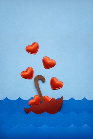 Creative valentines concept photo of umbrella with hearts floating in the sea on blue background. Stock Photo
